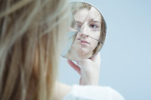 Image of woman with mental disorder holding broken mirror
