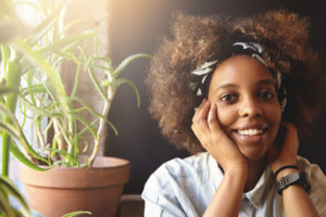 Fashionable student girl with Afro haircut wearing denim jacket, bandana and facial piercing, looking and smiling at camera with happy and cheerful expression, touching her face while relaxing indoors